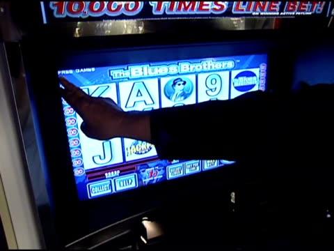 An offscreen man navigates a slot machine