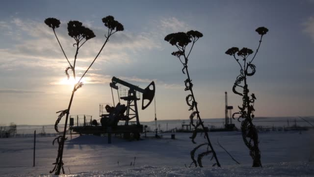 An oil pumping jack also known as a 'nodding donkey operates in a snow covered oilfield near a derrick right during drilling operations in an...