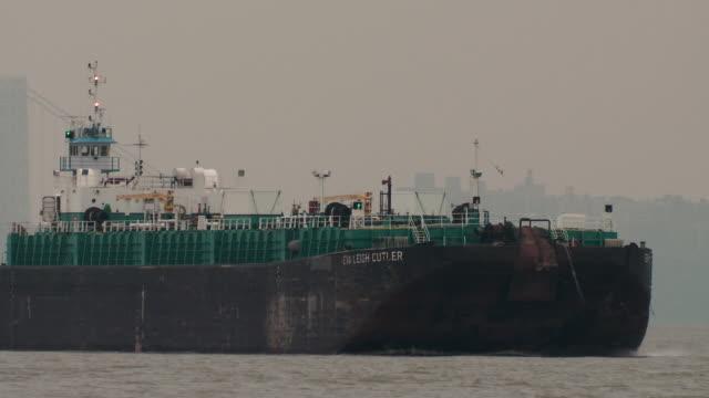 An oil tanker barge heads down the Hudson River, The George Washington Bridge is behind