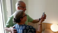 An old Indian couple combine together to take selfies, using a touchscreen on a smartphone