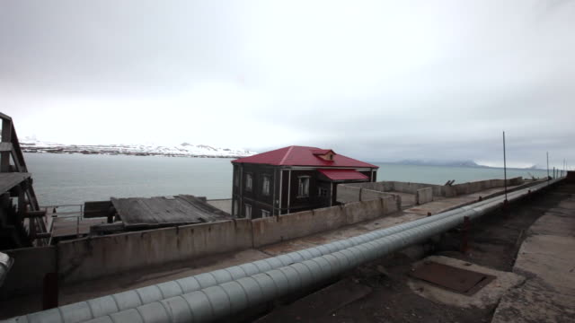 An old Russian house in Barentsburg, a Russian mining settlement on Svalbard archipelago with mountains covered by snow in the back