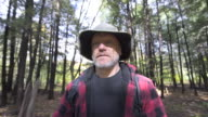POV of an older man going on a scenic hike through a forest in the mountains.