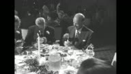 An older man wearing sunglasses and a boutonniere with a woman and girl at a banquet table with sign 'The Musicians Christmas Party' at rear / an...