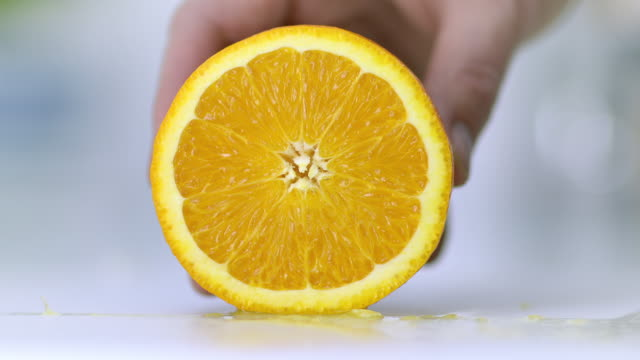 An orange placed on a white chopping board being held by hand and sliced very finely