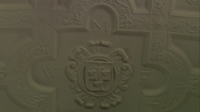 An ornate coat of arms is displayed on ceiling plasterwork. Available in HD.