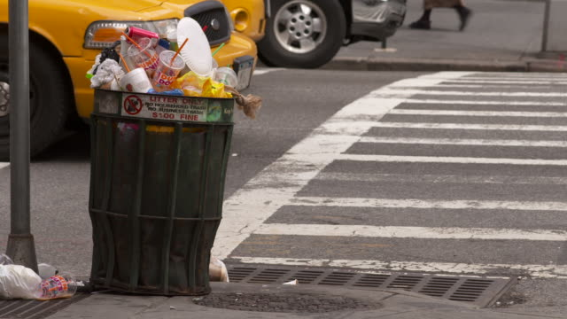 An overflowing trash can sits on a street corner while cars and people pass by.
