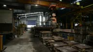 An overhead crane moves a ladle filled with molten steel for pouring into a mold in the foundry at IXL Industries A freshly filled mold of molten...