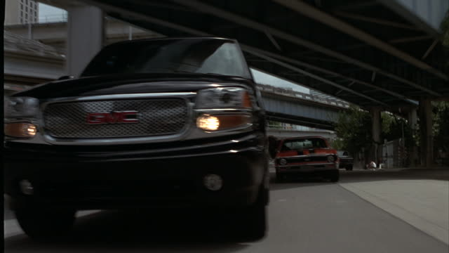 An SUV is chased by several muscle cars through an industrial area.