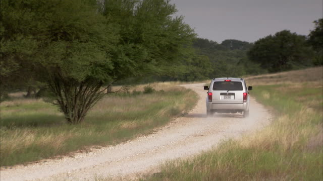 An SUV straddles ruts on a dusty dirt road. Available in HD.