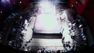 An time lapse of an American style professional wrestling ring as the crowd enter the arena
