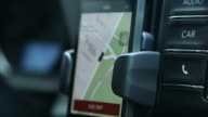 An Uber driver drives through New York New York US on July 7 Close up of a young Indian male driving Close up of iphone screen with the Uber app...
