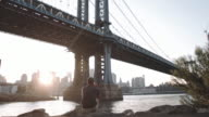 An unrecognizable man sits along The East River looking at The Manhattan Bridge at sunset.