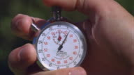 CU T/L Analog stopwatch in hand on sports field is starting and stopping / U.C.S.B., California, United States