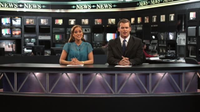 MS Anchors talking at newsroom desk, Dallas, Texas, USA