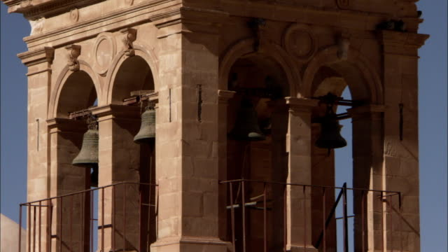 Ancient metal bells hang in the arches of the bell tower at Saint Catherine's Monastery in Mount Sinai Egypt. Available in HD.