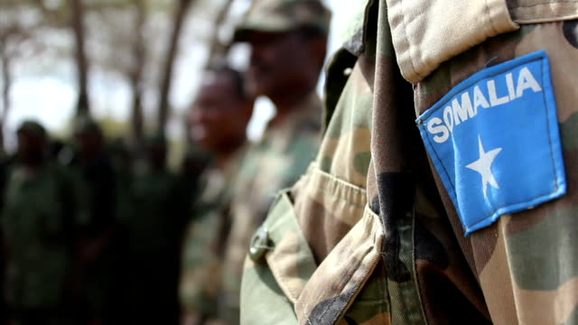 and Somali militia men lined up on the background Militia man's arm with Somali badge on July 31 2011 in Dhoobley Somalia
