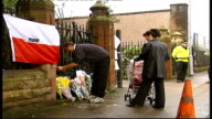 Glasgow St Patrick's Church EXT Man tying Polish flag onto railings outside Catholic church where body of Angelica Kluk was found Bunches of flowers...