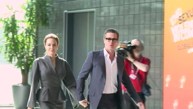 Angelina Jolie and husband Brad Pitt arrive at the final day of of a summit in London aimed at ending sexual violence in war with US Secretary of...