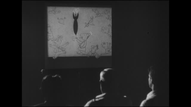 HD Angled WS BEHIND Three men sitting in dark watching slide show projected on screen 'How To Live With The Atom' produced by National Committee of...
