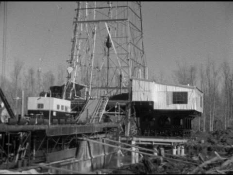 Angled WS Derrick oil rig base on barge w/ attached awning manufactured building off back unidentifiable male rig worker in hard hat walking up...
