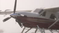 HD Angled MS Docked white amp red modern seaplane w/ moored boat in thick fog BG PAN Aircraft floating dock moving w/ water
