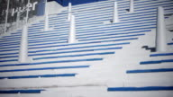 Angled MS DOLLY LEFT Blue white grandstand bleachers rising steeply w/ railings