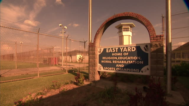 HD *Angled WS East Yard Home of religion education moral rehabilitation and sports champions freestanding sign next to prison fencing top of guard...