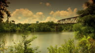 Angled WS Heavily foliaged banks of Warrior River w/ MobileOhio Railroad truss Bridge round water tower above treetops in distant BG No people or...