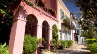 HD Angled WS Historical pastel row houses historic homes sidewalk some w/ wrought iron balconies No people