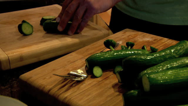 Angled MS Male hands holding slicing wet cucumber on wooden cutting board group of cucumbers on second board FG Healthy Lifestyle diet fruits...