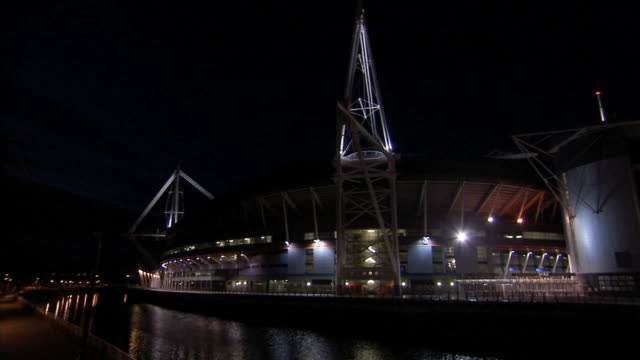 NIGHT HD VARICAM Angled WS Millennium Stadium w/ lighted modern design beam masts extending from structure single person jogging walking south west...