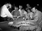 Angled WS People placing bets on Roulette table w/ stacks of chips wheel FG female male betting chips using 'system' MS Male making notes in small...