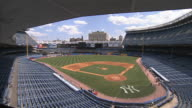HA Angled WS Empty baseball park blue left field seats PAN Manicured grass field to right field seating Yankees maintenance truck workers by dugouts...