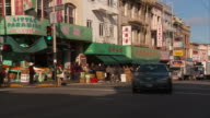 CHINATOWN HD Angled WS Produce store on street corner signs w/ Chinese characters unidentifiable people walking standing boxes shelves w/ fruits...