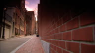 Angled CU Red bricks on building REVERSE PAN Narrow empty city residential street Mixed architecture vintage lamppost No cars No people