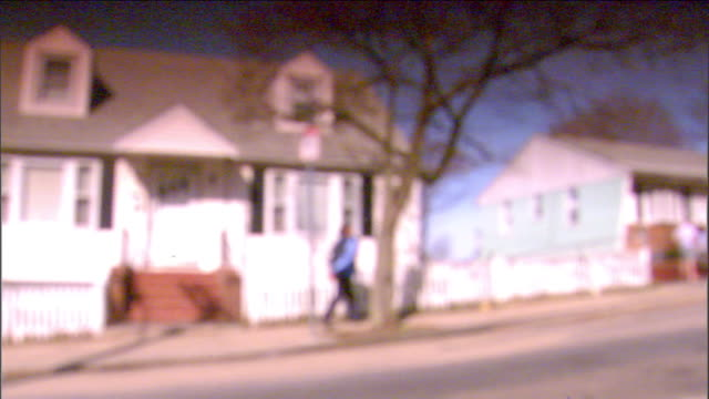 Angled WS REVERSE PAN Houses on sloping street neighbors standing outside unidentifiable male walking up sidewalk IN FOCUS WS Small house with white...