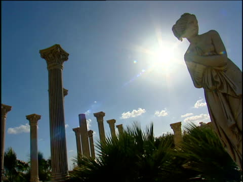 Angled shot of statue of ancient Greek goddess and classical pillars against bright blue sky palms wave gently in breeze as sun beams over scene Paralimni