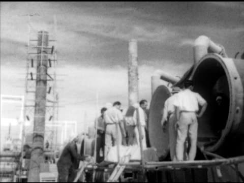 Angled WS Structure under construction men standing on scaffold checking interior of large pipes man sorting attaching hoses to metal container...