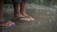 TD Angled MS Two pairs of Filipino children feet standing in flipflops on concrete walk in rain Typhoon season flooding flood PAGASA name Pepeng...