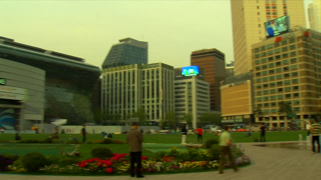 Angled WS Unidentifiable people in Seoul Plaza w/ rising water fountain city buildings some w/ large monitors displaying images BG REVERSE PAN/PAN...