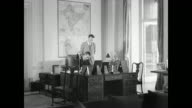 Angled WS Viceroy's House VS Lord Louis Mountbatten signing papers at desk walking wife Edwina and Indians
