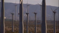 HD * Angled MS Wind farm group of wind turbines turning dirt landscape w/ shrubs mountains BG Green energy alternative Global Warming windmill...