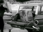 Angled WS Woman in parking lot behind open back of Ford Falcon station wagon lifting filled brown paper bag of groceries out of cart placing next to...