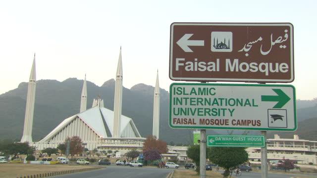 Angled XWS Shah Faisal Masjid w/ bilingual direction signs Faisal Mosque Islamic International University FG Margalla Hills in smog fog BG South Asia...