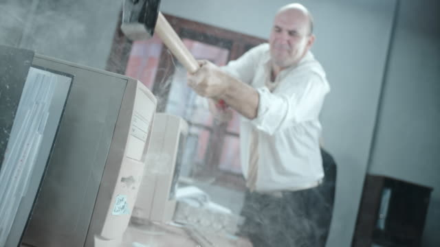 SLO MO Angry business man destroying his computer with hammer