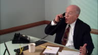 MS Angry businessman in office yelling into phone, hanging up, banging on desk, and throwing crumpled paper/ New York City