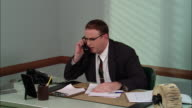 MS Angry businessman in office yelling into phone, hanging up, banging on desk, getting up and leaving/ New York City