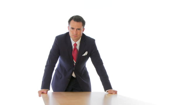 Angry businessman standing over table