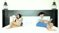 Angry Couple On The Bed And Using Tablet