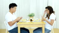 Angry couple using telephone on dining table